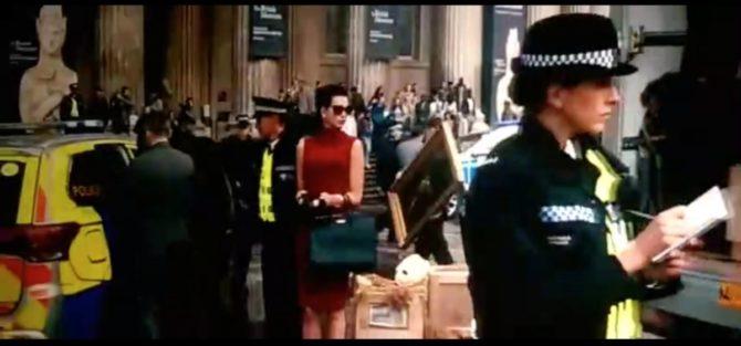Cena onde a mulher bem-vestida aparece em destaque.